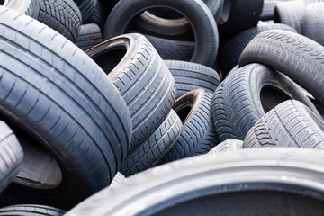 Close-up of used and old car tires with worn down treads randomly piled up in a stack