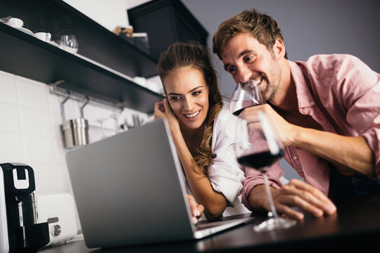 Young couple relaxing in kitchen with wine and laptop. Love, technology, people concept.