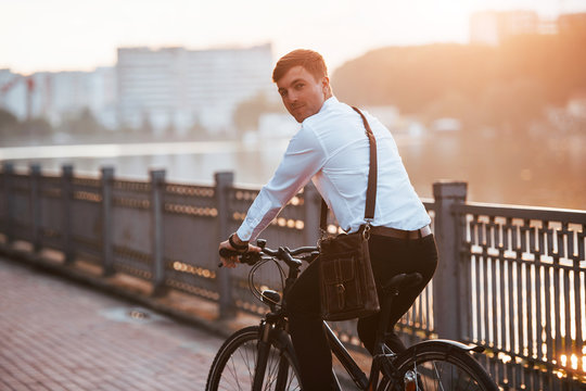 Feeling good. Businessman in formal clothes with black bicycle is in the city