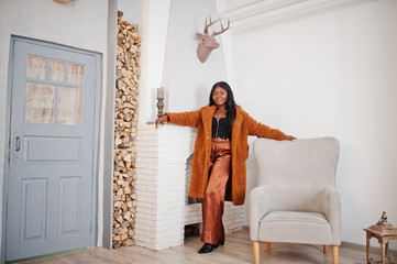 Stylish african american woman in orange coat posed at room against fire place.