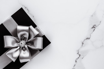 Luxury holiday gifts with silver silk ribbon and bow on marble background Fototapete