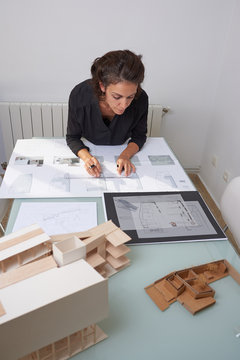 Young woman works as an architect in an office. She is brunette and Latina has a black shirt and different jobs on her table.