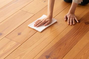 木目の床を雑巾で拭く若い女性の手元