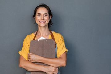 Woman entrepreneur in apron looking at camera