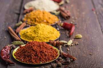 Heaps of various ground spices in little plate on wooden background. Georgian spices, Indian spices, Arabian spices. Spice variety. Herbs and spices Fototapete