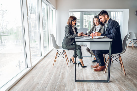 Wide angle of group business people in bright spacious modern office . Young businessman and businesswoman sitting at the desk in design studio with woman sales manager. Work with client concept