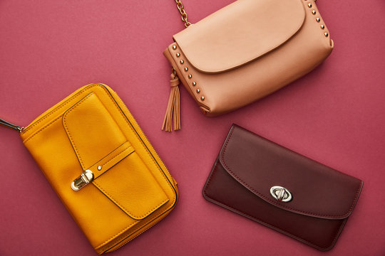 top view of leather and stylish bags isolated on crimson