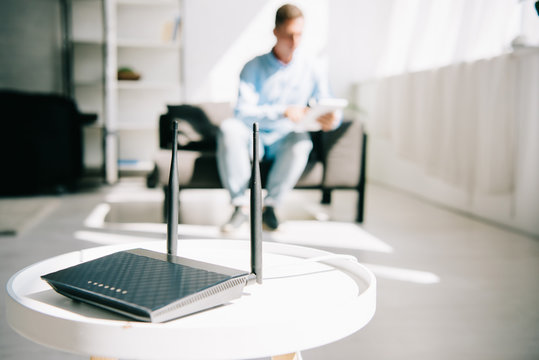 selective focus of black plugged router on white table and businessman sitting on sofa