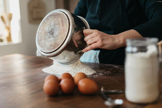 Chef pouring flour on a kitchen table preparing fresh pasta