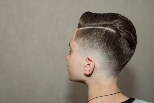 Stylish modern retro haircut side part with mid fade with parting of a school boy guy in a barbershop on a brown background
