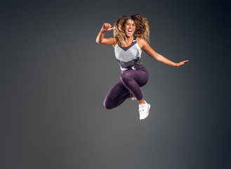 Cheerful happy woman is showing her performance at photo studio on the grey background.