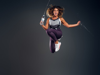 Exited cheerful woman is jumping at studio while holding the bottle of water over grey background.