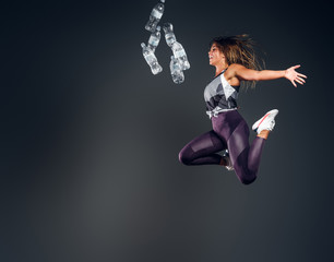 Happy smiling woman trow away bottles of water while jumping at grey studio background.
