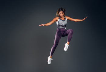 Happy attractive woman in activewear is jumping at studio over grey background.