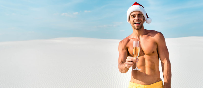 panoramic shot of sexy man in santa hat holding champagne glass on beach in Maldives