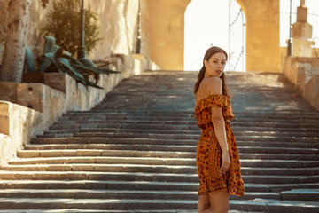 young brunette woman wearing a floral pattern summer dress, walking down a staircase, looking back over her shoulder, at a castle in Artà on Mallorca