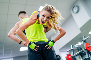 Strong man bodybuilder is lifting a blonde fitness girl over his shoulder. Man looking in the camera. Gym background. Bright sportswear.