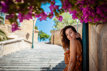 young brunette woman wearing a floral pattern summer dress, leaning against a lamp post next to a stone wall and colorful blooming bushes, in Artà on Mallorca