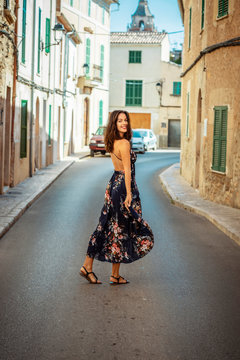brunette young woman in a floral print dress walking on a calm Spanish village street