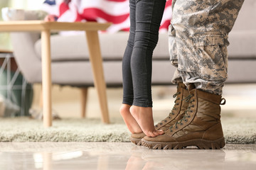 Girl standing on feet of her military father at home