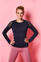 Young woman in a sports sweatshirt in black color and pink leggings, on a pink background in the studio.