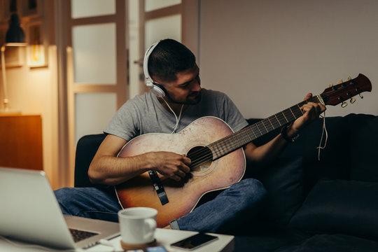 man playing guitar at his home