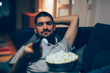 man watching tv late night in his apartment