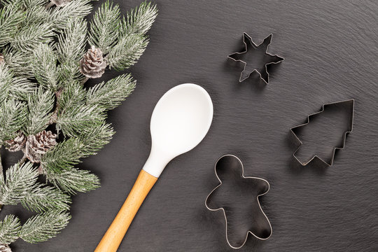 Gingerbread man, fir, snowflake cookie cutters and spoon for Christmas cooking or baking with snowy fir branches with cones over slate background. Flat lay, top view.