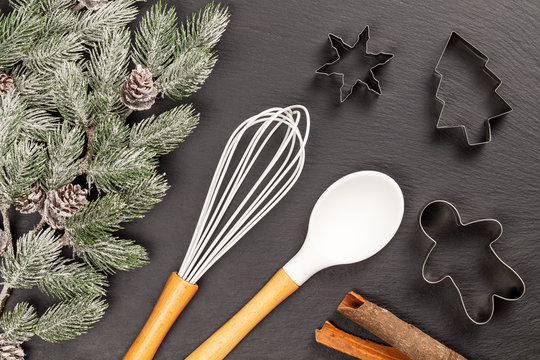 Gingerbread man, fir and snowflake cookie cutters with spoon, whisk and cinnamon sticks for Christmas cooking or baking with snowy fir branches with cones over slate background. Flat lay, top view.