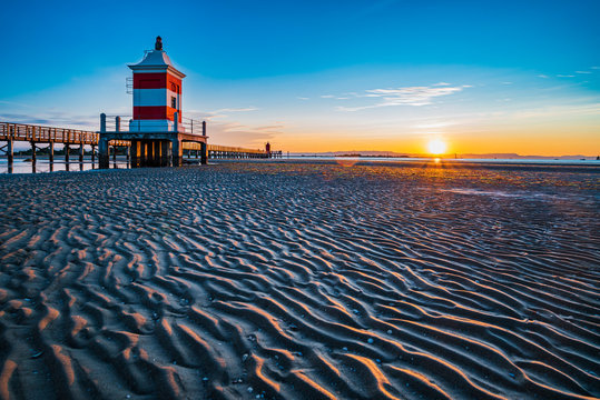 Sunrise over the sea. The lighthouse of Lignano Sabbiadoro and the games of sand and colors. Italy