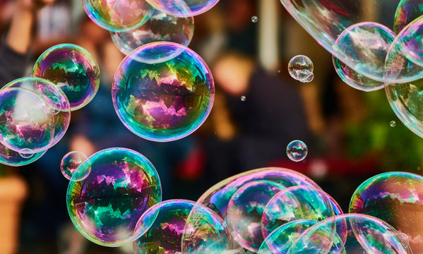 Metallic glowing colorful soap bubble in the air in front of a blurry abstract background