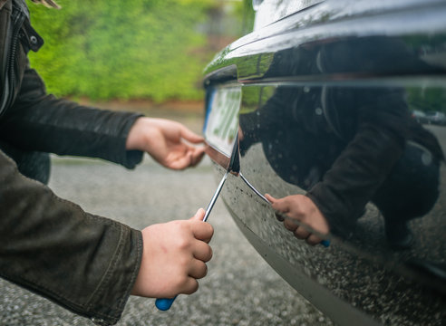 person steals the license plate on a car with a screwdriver