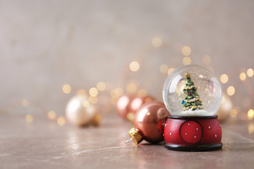 Snow globe with Christmas tree and decorations on marble table against festive lights, space for...