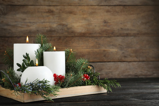 Beautiful Christmas composition with burning white candles on wooden background. Space for text