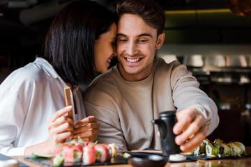 Aluminium Prints Sushi bar selective focus of cheerful man holding black bottle near woman and sushi