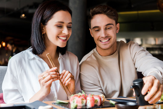 cheerful man holding black bottle near woman and sushi