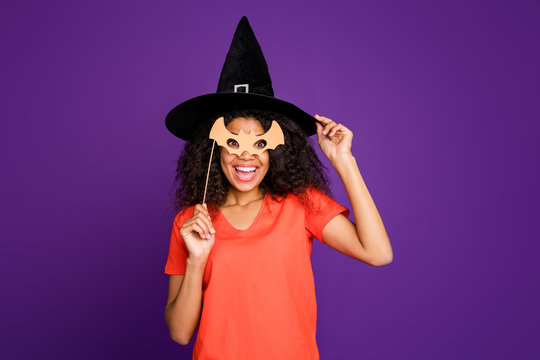 Photo of cheerful positive cute charming nice overjoyed girlfriend pretending to be witch in mask of bat pleased with such masquerade wearing orange t-shirt cap isolated over vivid purple color