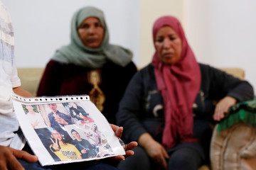 Mokhtar Hmidi, the father of Fakher, shows pictures of his son during an interview with Reutersin Thina district of Sfax
