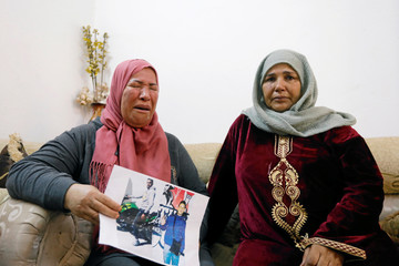Zakia, mother of Fakher Hmidi, carries his pictures as she reacts during an interview with Reuters in Thina district of Sfax