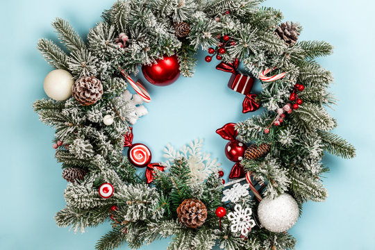 Christmas wreath or crown composition with frozen fir garlands, spheres, sweets and candy cane over a blue background. Flat lay, top view with copy space..