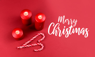 Merry Christmas sign stock images. Red Christmas background with candles and candy cane. Christmas still life concept. Christmas candy cane stock images