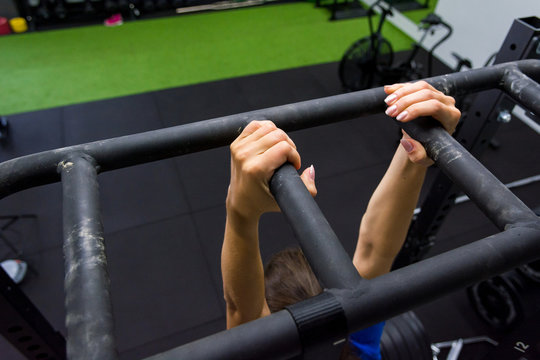 Detail of female hands gripping bar rig and doing leg raises in local gym.