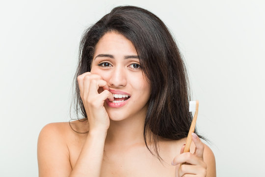 Young hispanic woman holding a toothbrush biting fingernails, nervous and very anxious.