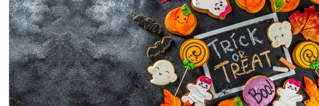 Halloween background with Funny Gingerbread Cookies - pumpkins mummy, zombies, ghosts, spiderweb. Top view with copy space.
