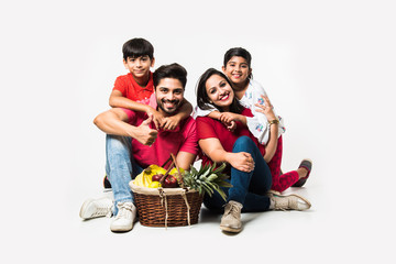 Indian young Family of four going for Picnic - standing over white background with fruit basket, mat, football and drinks. selective focus