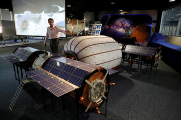 Robert Bigelow, (L) founder and president of Bigelow Aerospace, speaks by a 1:6 scale mock-up of a base space station featuring a B330 inflatable unit during a tour of Bigelow Aerospace in North Las Vegas