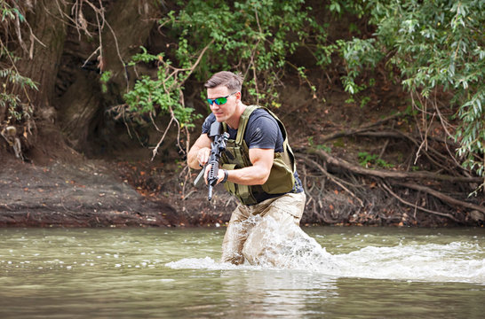 One day commando - wades through the water with a rifle