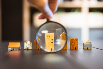 Fototapeta Hand holding magnifying glass and looking at house model, house selection, real estate concept. obraz