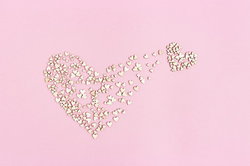 Small heart emerges from large one. Birth of new love. Concept of love. Many small wooden hearts on pink background. Flat lay.