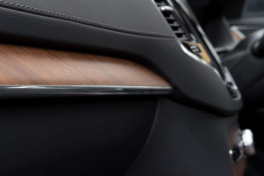 Detailed, shallow focus of the expensive american walnut trim seen on a glovebox of a European made, luxury SUV.